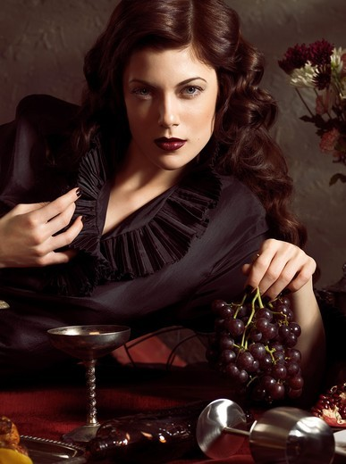 Stock Photo: 1566-756985 Artistic photo of a beautiful woman lying on a festive table with grapes in her hand