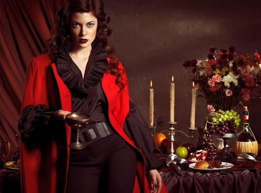 Stock Photo: 1566-756986 High fashion photo of a beautiful woman standing with a glass of wine at a table with remains of a festive dinner