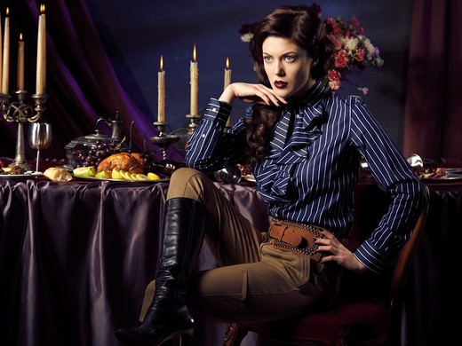 Artistic high fashion photo of a beautiful woman sitting at a table with remains of a festive dinner : Stock Photo