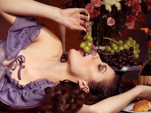 High fashion photo of a beautiful woman lying on a festive table and eating grapes : Stock Photo