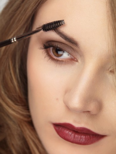 Stock Photo: 1566-757034 Closeup of a woman´s face with makeup being applied to her eyebrows