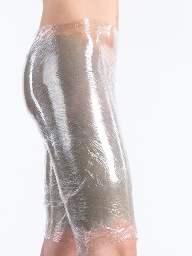 Woman with bentonite clay mask and plastic body wrap on her thighs and buttocks : Stock Photo