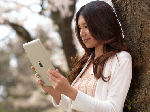 Young Asian woman with iPad in a park under a cherry tree : Stock Photo