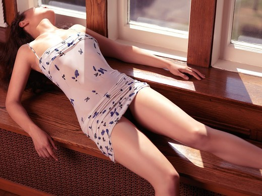 Sensual photo of a beautiful young woman in wet short summer dress lying on a window sill : Stock Photo