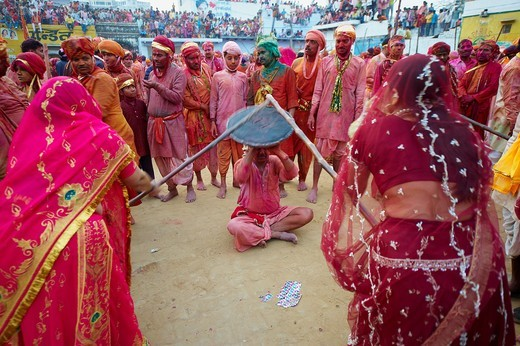 India, Uttar Pradesh, Holi festival, color and spring festival, celebrate the love between Krishna and Radha  Hundreds of women wear bamboo stick and during Holi, the village women have the freedom to hit men who are only allowed to protect themselves : Stock Photo
