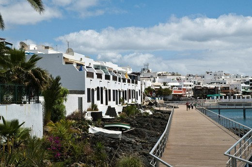 Stock Photo: 1566-761252 Puerto del Carmen habour PUERTO DEL CARMEN LANZAROTE People walking walkway waterfront promenade restaurant cafe seafront