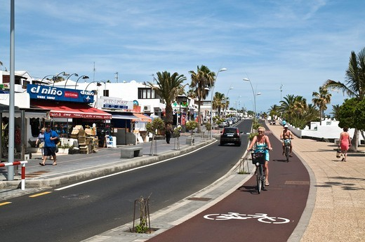 Stock Photo: 1566-761311 PUERTO DEL CARMEN LANZAROTE Tourist cyclists on pushbikes cycle path pavement