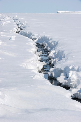 Sea ice crack in the spring - often run between geographical points on the land which act as natural stress points, these cracks form the starting points of sea ice breakup. : Stock Photo