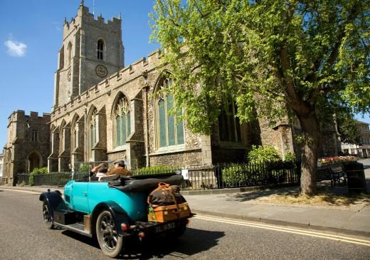 Stock Photo: 1566-763036 Classic veteran car passing Church of Saint Peter, Sudbury, Suffolk, England