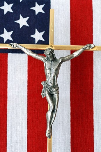 A Crucifix with an American flag in the background  This Crucifix lay on the casket of an American War Veteran : Stock Photo