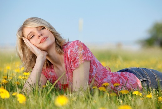 Stock Photo: 1566-765858 young blonde woman lying on meadow