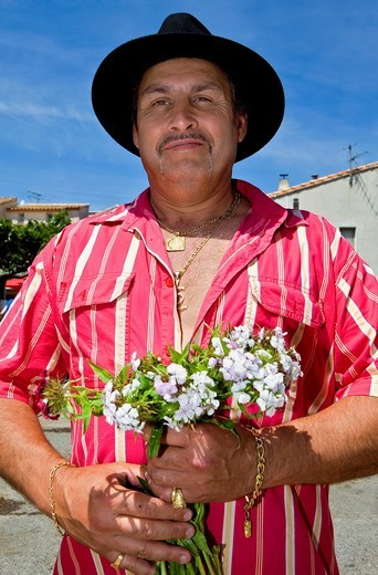 Pilgrim Man with flowers for Sainte Sara Procession during annual gipsy pilgrimage at Les Saintes Maries de la Mer may,Camargue, Bouches du Rhone, France : Stock Photo