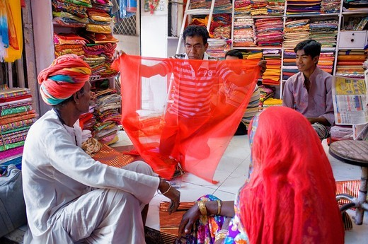 Stock Photo: 1566-767137 Vendor and customer in Clothing store,Sardar Market,Jodhpur, Rajasthan, India