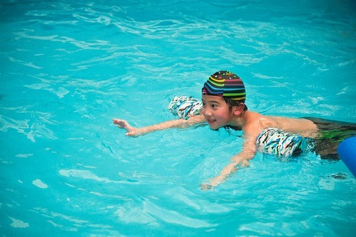 A boy enjoying a swimming session in a pool : Stock Photo