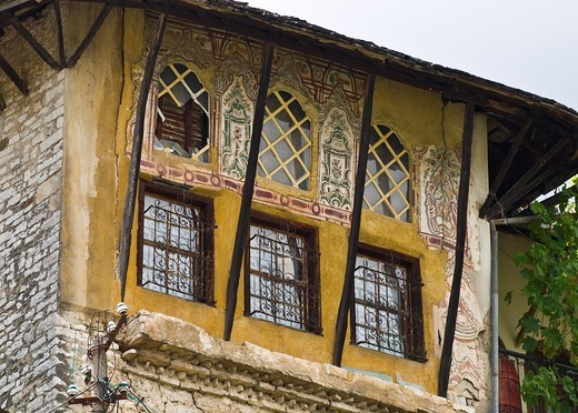 Stock Photo: 1566-767764 Traditional, ottoman style, painted decoration and wrought iron grills on a house in the old town of Gjirokastra in southern Albania