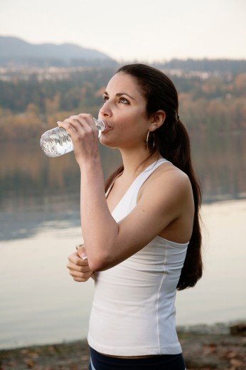 Stock Photo: 1566-768247 A young athletic woman drinking from a bottle of water, Inlet Park, Port Moody, British Columbia, Canada