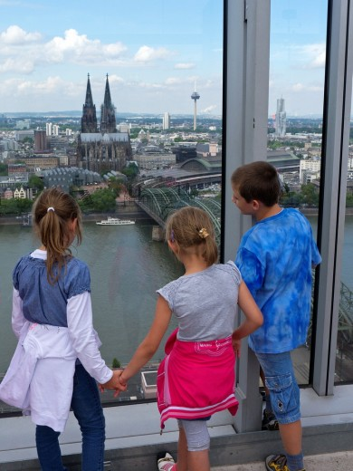 Children looking at skyline view of Cologne from observation platform in high rise building : Stock Photo