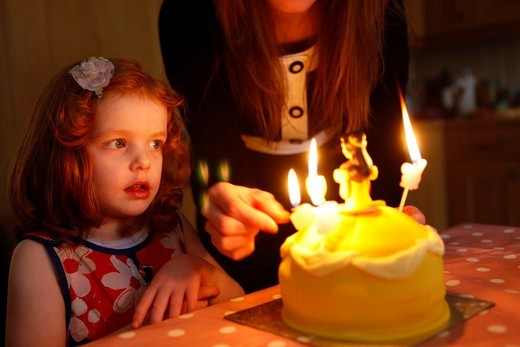 Stock Photo: 1566-772754 A 4 year old girl with ginger hair celebrates her birthday with a birthday cake