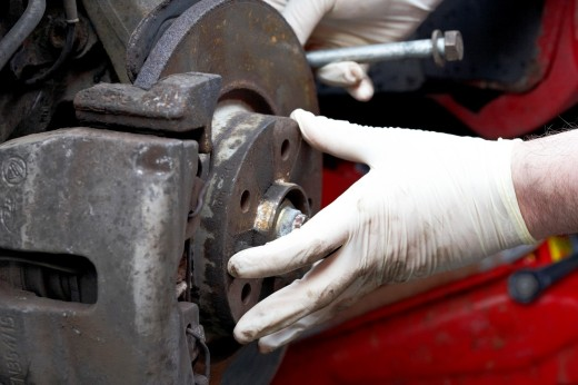 mechanic wearing rubber gloves performing car maintenance on a rusty old wheel hub : Stock Photo