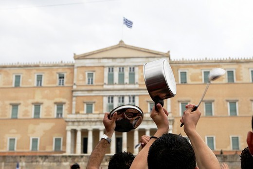A protester holds a casserole in front of the Greek Parliament during a peaceful rally attended by thousands called through a social networking site- modeled on protests by young people in Spain  People protest against the new austerity measures plan of t. A protester holds a casserole in front of the Greek Parliament during a peaceful rally attended by thousands called through a social networking site- modeled on protests by young people in Spain  People protest against the new austerity measur : Stock Photo