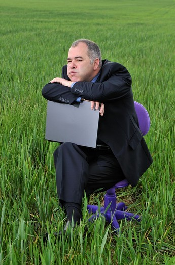 businessman bored at a green field with a laptop : Stock Photo