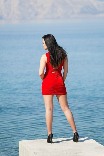 Stock Photo: 1566-782915 Attractive young woman is standing on the edge