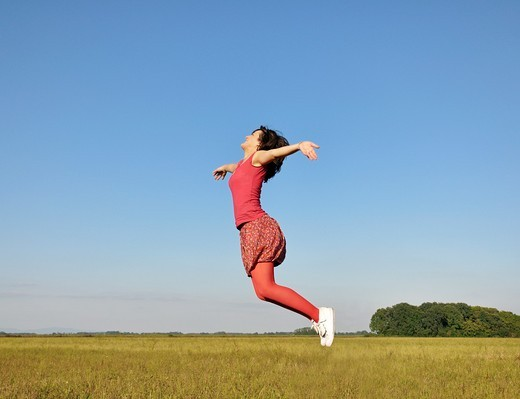 Young woman jumping in air : Stock Photo