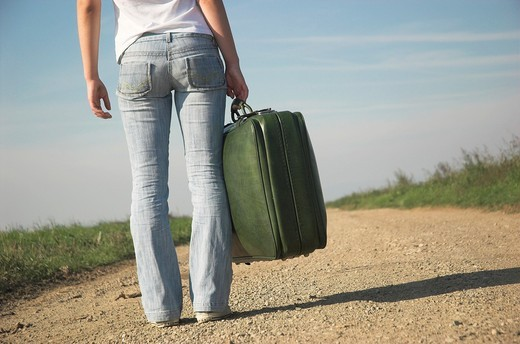 Young woman carrying suitcases on country road, rear view : Stock Photo