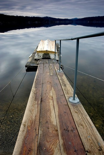 A fine art image of a boat ramp leading to a dock on a lake : Stock Photo