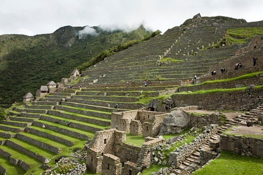 Stock Photo: 1566-786530 View of agricultural terraces in the western agricultural sector of the Machu Picchu complex, Watchman´s Hut at the top of the hill, and storage ´Qolqas´ to the left  Machu Picchu, Peru
