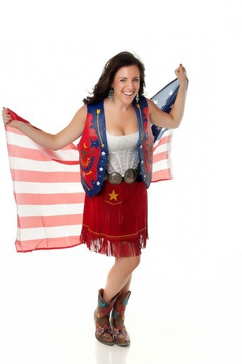 Young woman in cowgirl outfit waving american flag : Stock Photo