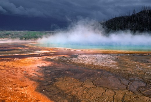 Stock Photo: 1566-786793 Grand Prismatic Spring with colorful algae and approaching storm clouds, Midway Geyser Basin, Yellowstone National Park, Wyoming, USA