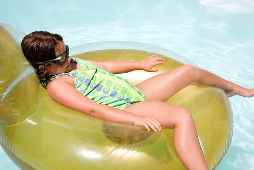 Stock Photo: 1566-787506 Girl on Lilo in swimming pool