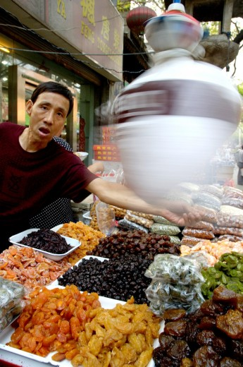 Man selling dried fruit at the market, Daqingzhen Si, Muslim District, Xian, Shaanxi, China : Stock Photo