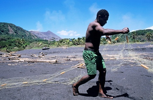 Fisherman on a black sand beach preparing his nets, Sulphur Bay Village, Tanna Island, Vanuatu : Stock Photo