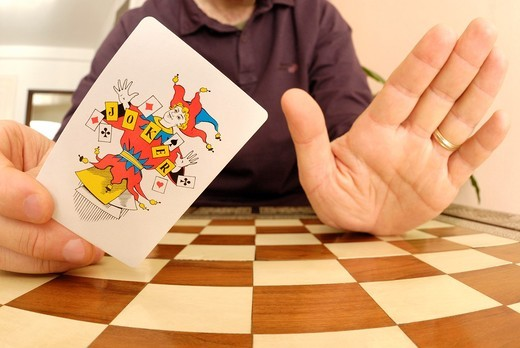 Stock Photo: 1566-791282 Man holding up a joker playing card