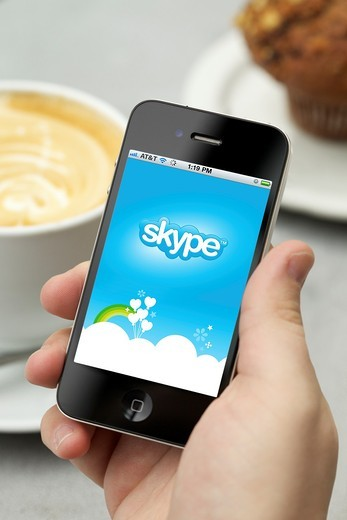 Man hand holding an iPhone 4 showing Skype application at a cafe : Stock Photo