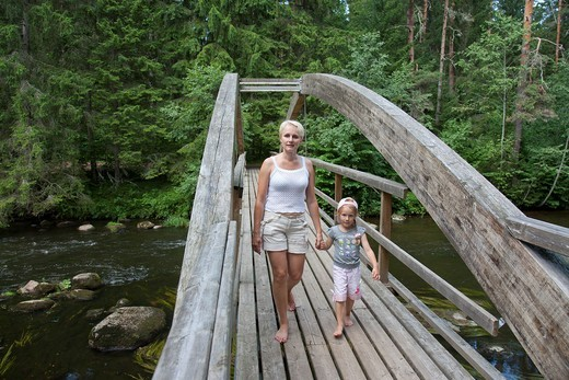 Mother With Kid Walking Over Wooden Bridge Holding Hands, Põlva County, Estonia, Europe : Stock Photo