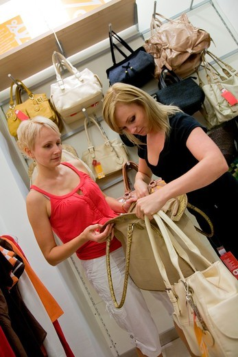 Young women shopping and comparing different nylon shoulder bags in store : Stock Photo