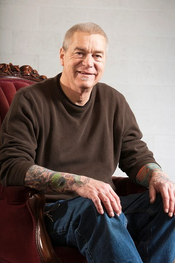 Stock Photo: 1566-797147 Portrait of a clean-cut, tattooed, mature man in the studio - smiling expression