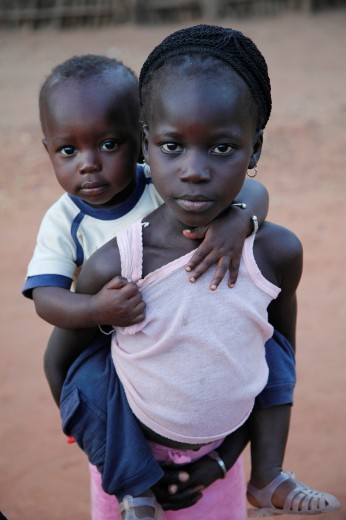 young african girl carrying her brother on her back, The Gambia, Africa : Stock Photo