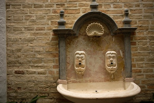 Stock Photo: 1566-798705 A fountain with two human faces and a scallop shell is displayed in Santa maria de la Asuncion church in Carmona, Seville province, Andalusia, Spain, April 19, 2011