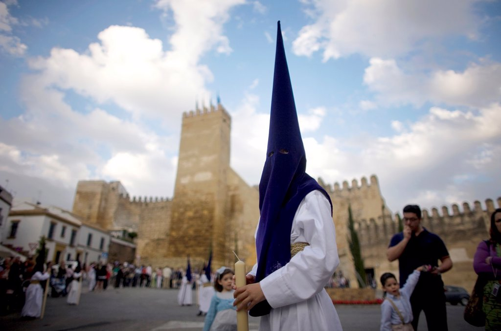 Stock Photo: 1566-798717 A penitent participates in an Easter Holy Week procession in front of the Alcazar fortress in Carmona, Seville province, Andalusia, Spain, April 19, 2011