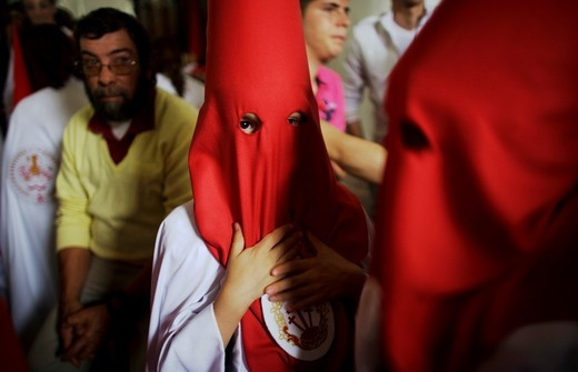 Penitents stand inside a church waiting to start an Easter Holy Week procession in Carmona, Seville province, Ansalusia, Spain, May 19, 2001  The procession was canceled because it was raining : Stock Photo