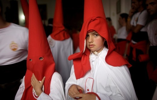 Stock Photo: 1566-798725 Young penitents stand inside a church waiting to start an Easter Holy Week procession in Carmona, Seville province, Ansalusia, Spain, May 19, 2001  The procession was canceled because it was raining