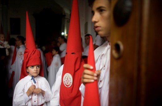 Stock Photo: 1566-798726 Young penitents stand inside a church waiting to start an Easter Holy Week procession in Carmona, Seville province, Ansalusia, Spain, May 19, 2001  The procession was canceled because it was raining