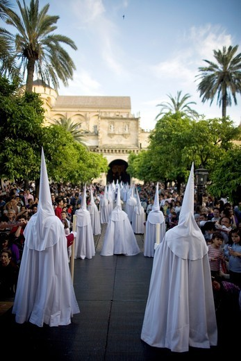 Stock Photo: 1566-798760 Penitents walk in the Orange Trees Court, Patio de los Naranjos in Spanish, in the Mosque-Cathedral of Cordoba during Easter Holy Week celebrations in Cordoba, Andalusia, Spain, April 18, 2011