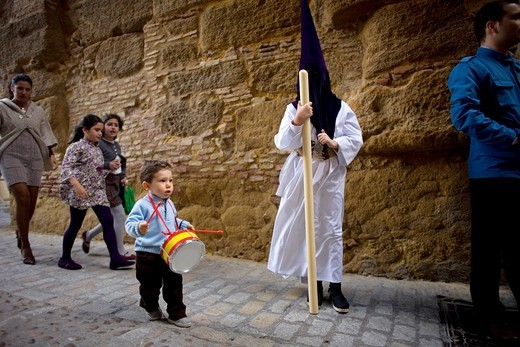 A boy plays a toy drum decorated with the Spanish flag as he passes a penitent during an Easter Holy Week procession in Carmona village, Seville province, Andalusia, Spain, April 19, 2011 : Stock Photo