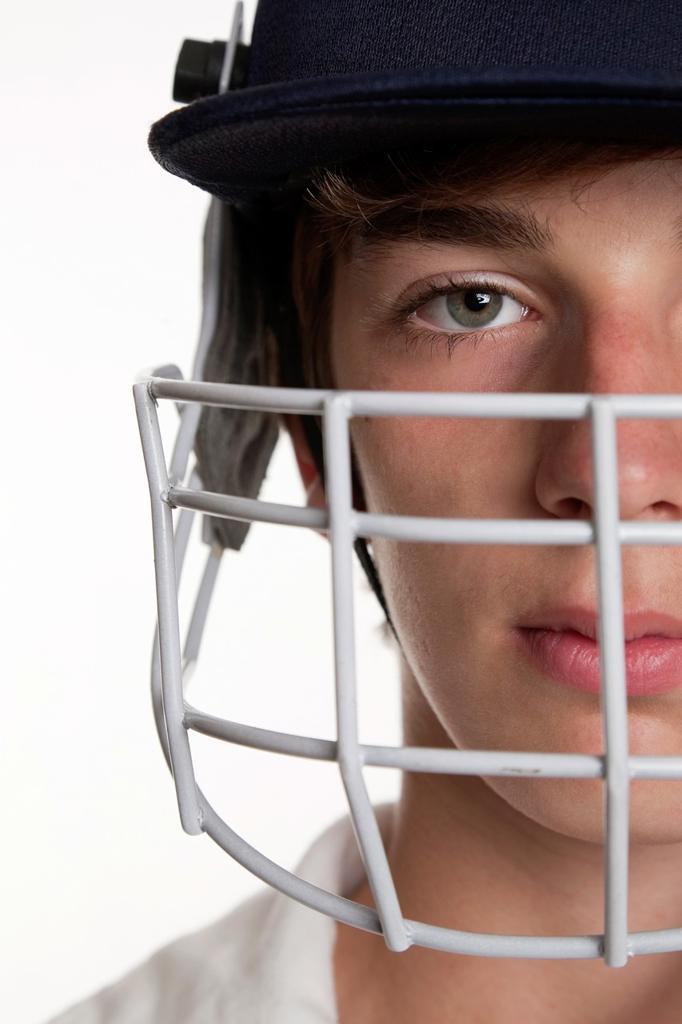 Stock Photo: 1566-804565 Portrait of teenage cricketer in protective helmet and visor
