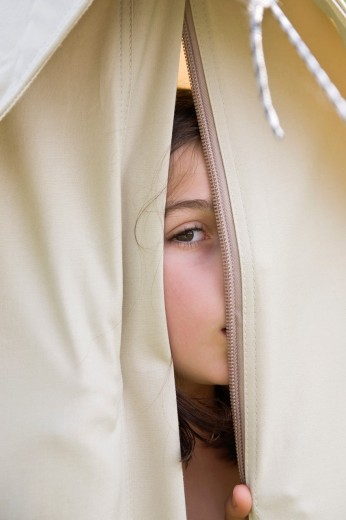 Stock Photo: 1566-804566 Young girl peeping through opening in a canvas tent